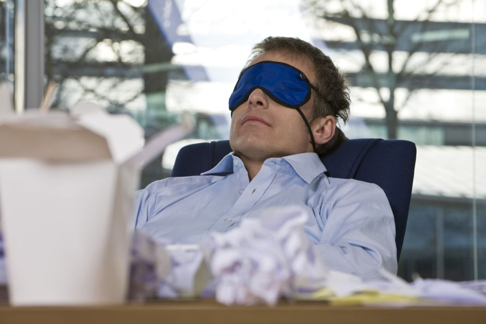 businessman taking a nap at his desk wearing a sleep mask